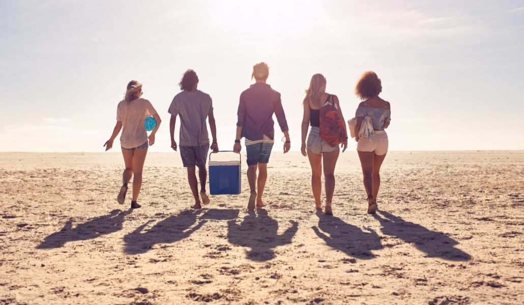 Friends-walking-on-the-beach-carrying-a-cooler-box-518909770_2313x1301